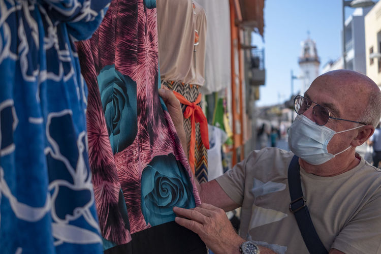 Close-up of senior man wearing mask looking at garment for sale at market