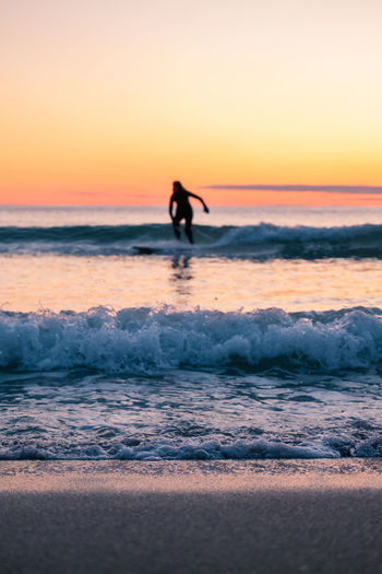 Silhouette woman surfing on sea against clear sky during sunset