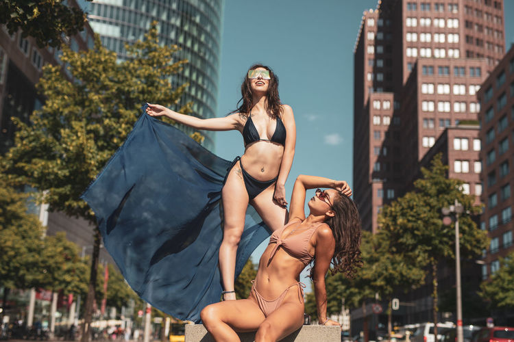 Young women wearing bikinis in city during sunny day
