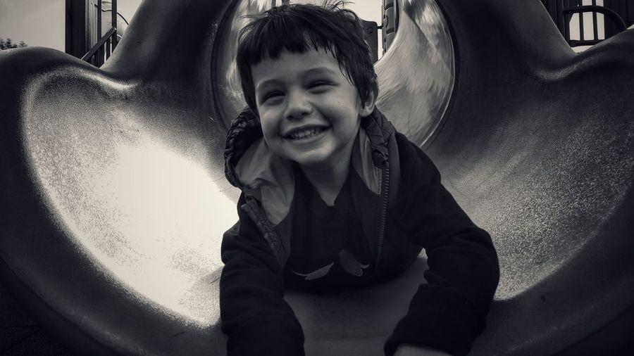 Close-up of smiling boy lying on slide at park