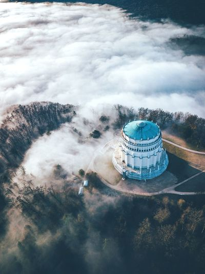 Digital composite image of building against cloudy sky