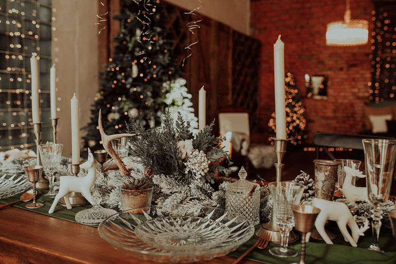 Chic christmas table setting in beige and wooden colors, glassware, candles. christmas interior