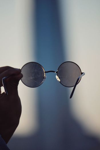 Close-up of hand holding sunglasses against blurred background