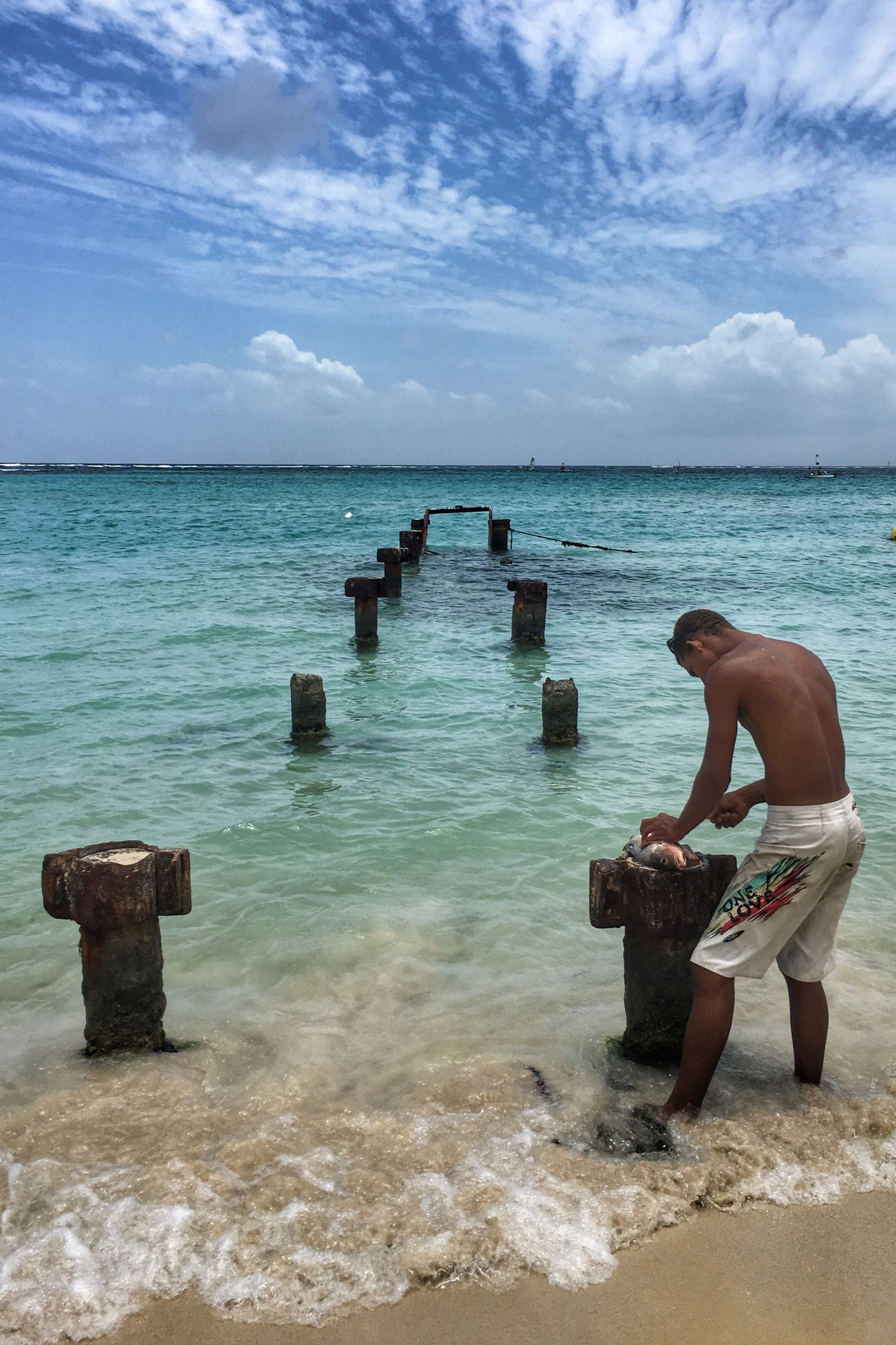 sea, water, horizon over water, sky, lifestyles, leisure activity, beach, cloud - sky, full length, shore, rear view, scenics, beauty in nature, tranquil scene, men, tranquility, nature, cloud