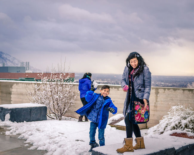 Family Playing With Snow While Standing On Building Terrace Against Cloudy Sky