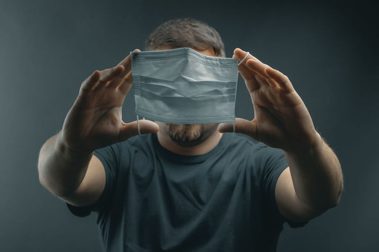 Portrait of man holding covering face against black background