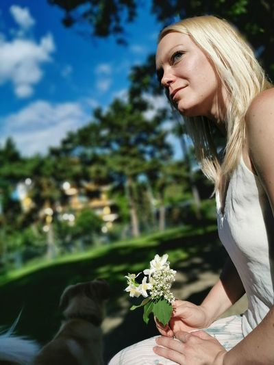 Side view of woman with flowers sitting at outdoors