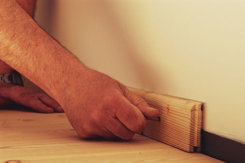 Cropped image of hands attaching wood on wall