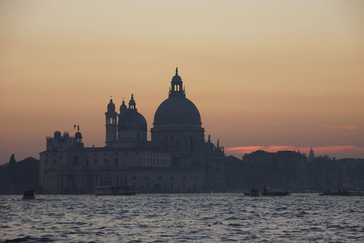 Santa Maria Della Salute By Grand Canal Against Sky During Sunset In City