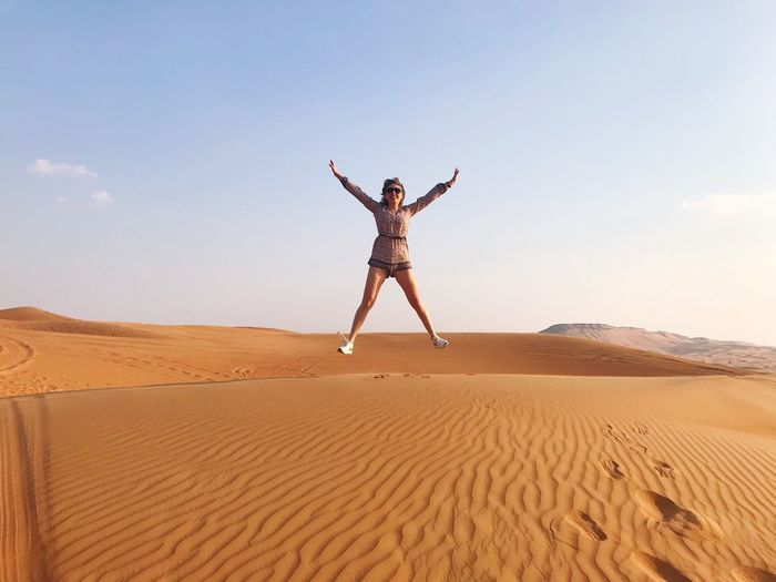 Cheerful woman with arms outstretched jumping at desert against sky