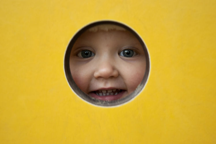 Young girl peeking though a hole on a playground. Child Childhood Cute Fun Innocence Looking At Camera One Person Peeking Smiling Yellow