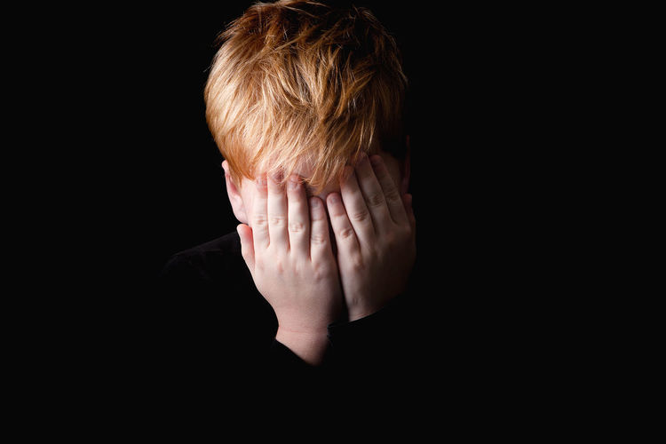 Close-up of boy covering face over black background