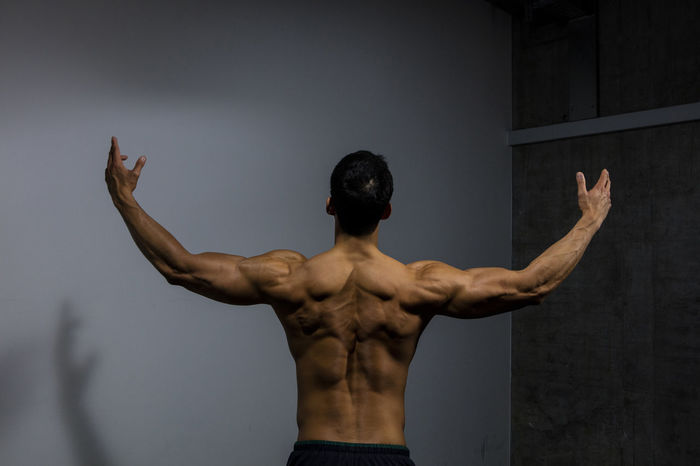 Male fitness model displays his muscular back muscles. Adult Asian  Athletic Back Human Body In Shape Man Masculinity Rear View Arms Raised Back Turned Body Building Deltoid  Fitness Fitness Model Handsome Male Model Muscles Muscular Build Strong Torso Traps Triceps Upper Body