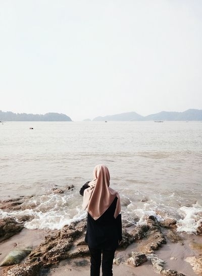 Rear View Of Woman Wearing Hijab Looking At Sea Against Clear Sky