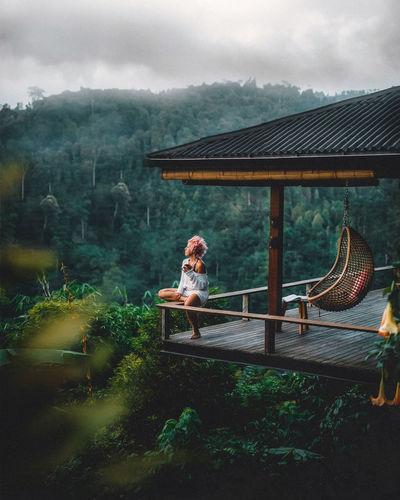 Woman sitting on railing in balcony