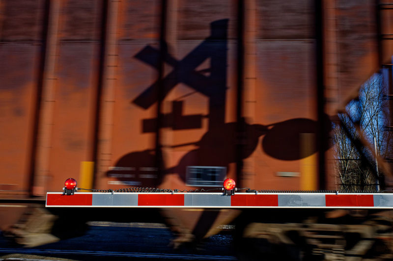 Rail crossing gate arm and a moving train. Abstract Blurred Motion Gate Arm Motion No People Outdoors Railroad Crossing Gate Shadow Of Crossing Signal Shadows Transportation