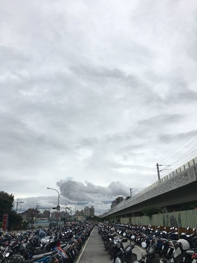 Group of people on road in city against sky