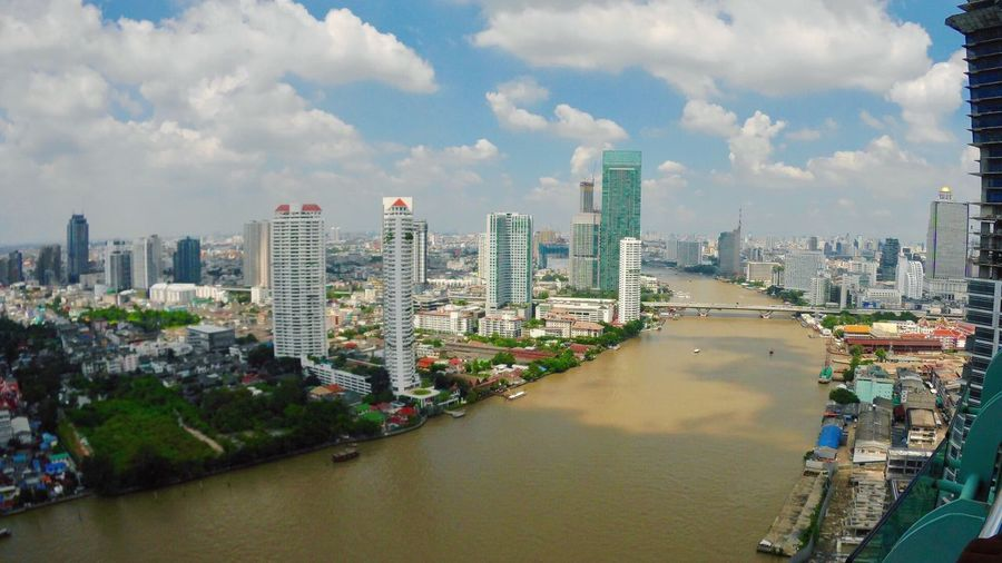 River Amidst Cityscape Against Sky