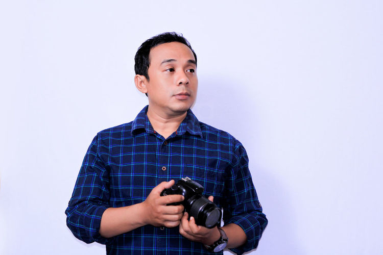 Portrait of young Asian Photographer White Background Technology Men Business Studio Shot Business Finance And Industry Mature Men Photographer Camera - Photographic Equipment Paparazzi Photographer SLR Camera Photographing Photography Themes