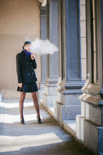 Young Woman Smoking While Standing At Corridor