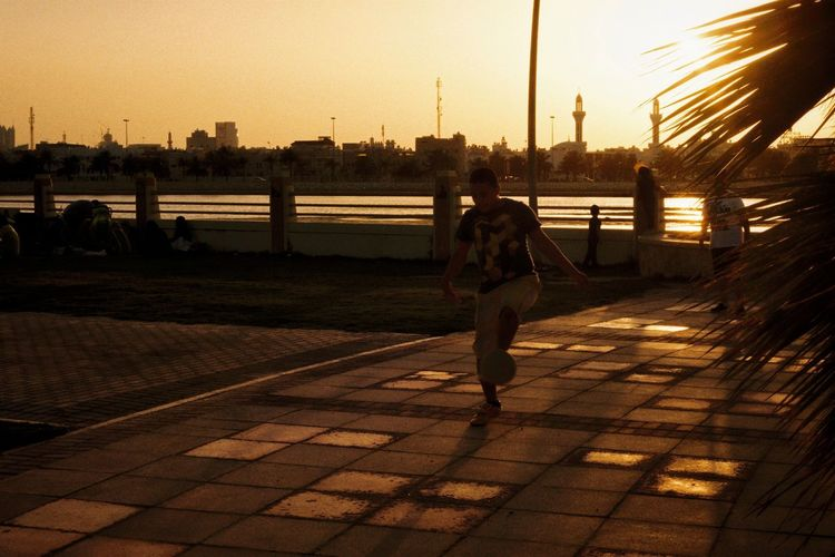 Rear view of woman standing by cityscape against sky during sunset