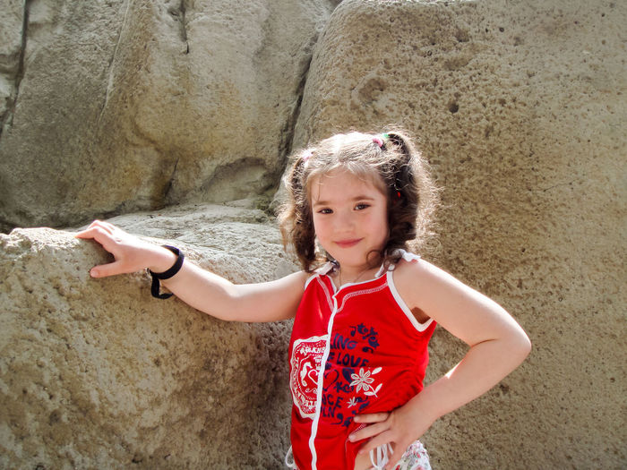 Portrait of smiling girl with hand on hip standing by rock formation