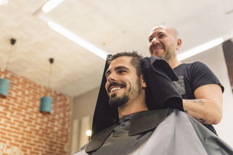 Low angle view of smiling barber and customer in salon