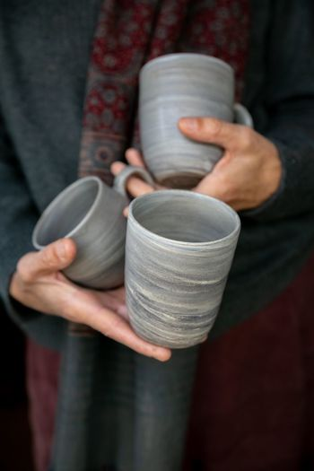 Midsection of person holding mugs