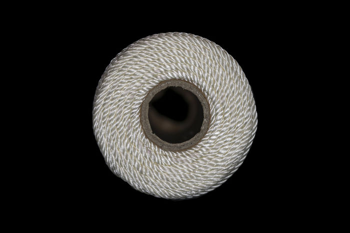 Closeup of the end of white string twine wrapped around a cardboard tube against a black background Black Background Cardboard Tube Circle Close-up Coil Rope String Studio Shot Tool Tube Twine White Wrapped