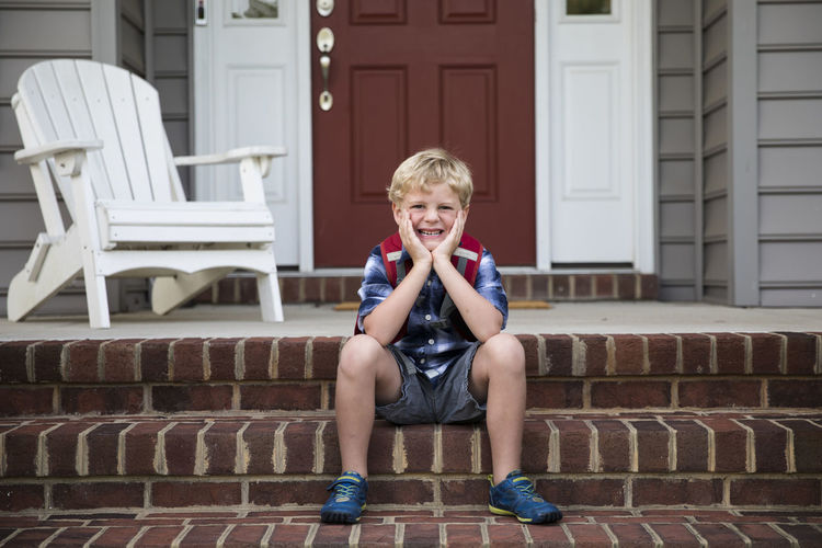 Portrait of smiling boy sitting outdoors