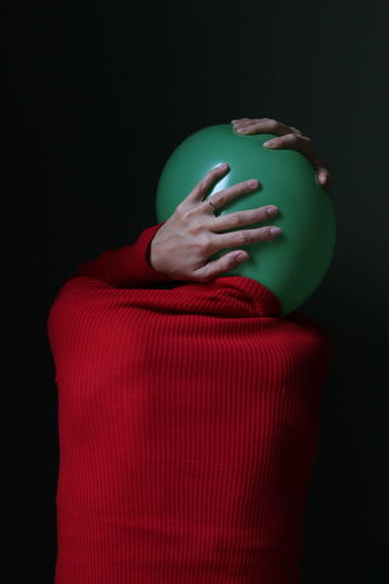 Rear view of person with balloon against black background