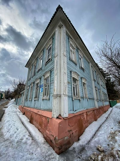 Built structure by snow covered building against sky