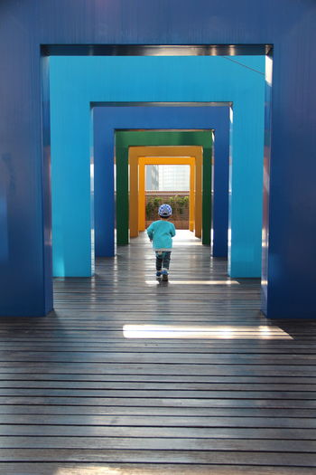 a running boy and blue frames Run Architecture Blue Sky Boy Building Built Structure Direction Door Entrance Frame Full Length Illuminated Leaving One Person Rear View The Way Forward Walking 10