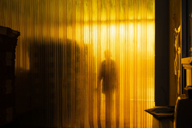 Yellow industrial plastic curtain entrance with shadow of worker and cardboard box package