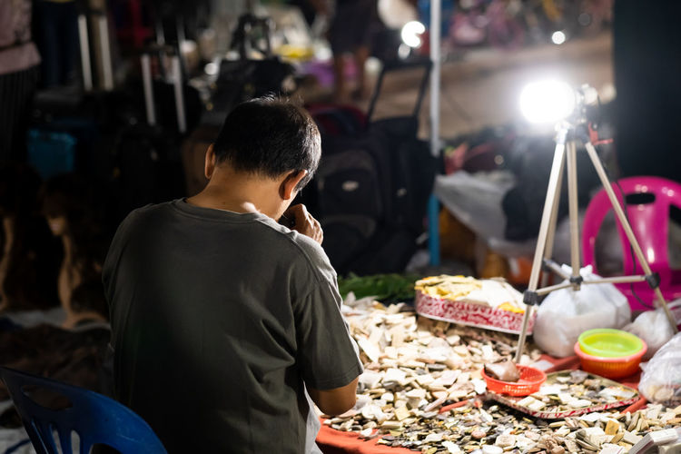 Rear view of man vendor at market during night