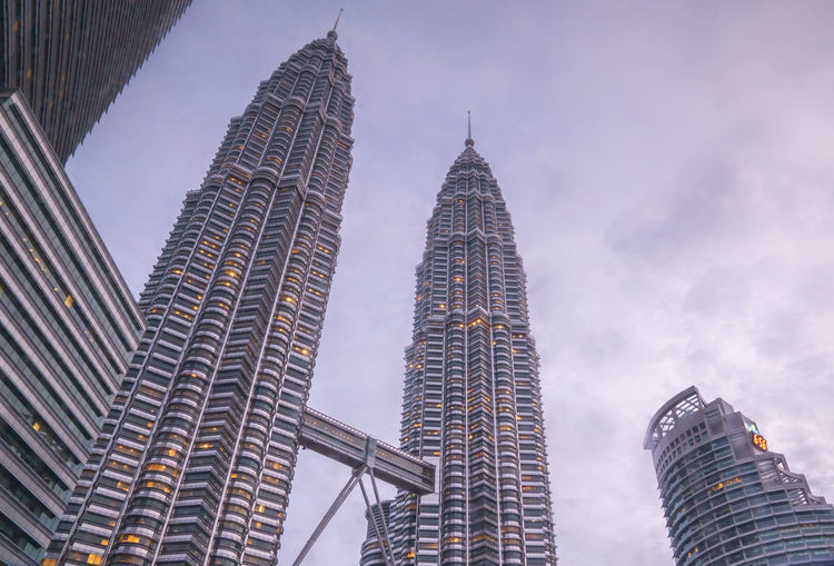 Low angle view of petronas towers against cloudy sky