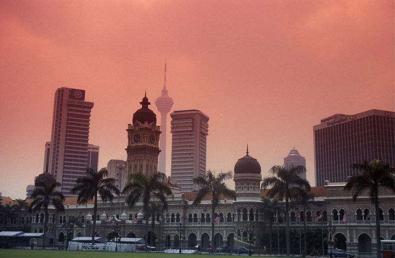 Menara kuala lumpur tower by mosque against sky during sunset