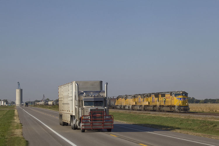 typical scene of transportation, with truck and heavy freight train in united states Delivery Hauler Heavy Duty Union Pacific Railroad Blue Sky Business Clear Sky Commercial Land Vehicle Copy Space Day Diesel Engine Freight Train Freight Transportation Land Vehicle Mode Of Transportation Motion Motor Vehicle Nature No People on the move Outdoors Road Semi-truck Sky Transportation Travel Truck Trucking Typical American