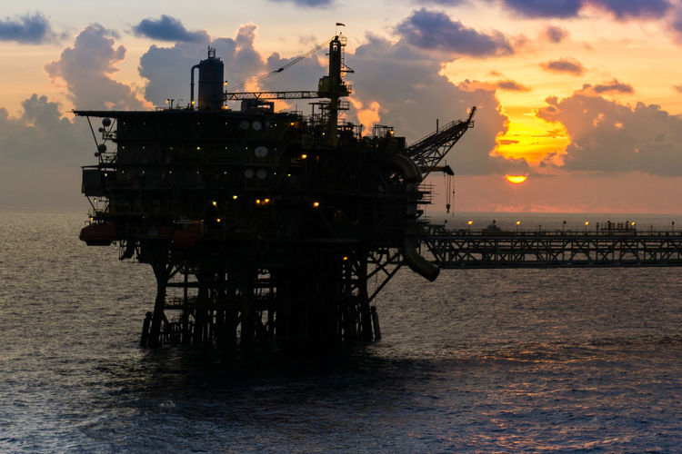offshore platform during sunset Golden Hour Evening Cloudy Ocean Horizon Wave Bridge Engineering Offshore Offshore Life Oil And Gas Petroleum Upstream Drilling Rig Offshore Platform Water Sea Oil Pump Oil Industry Sunset Industry Business Finance And Industry Crude Oil Oil Field Oil Natural Gas Oil Well Fossil Fuel