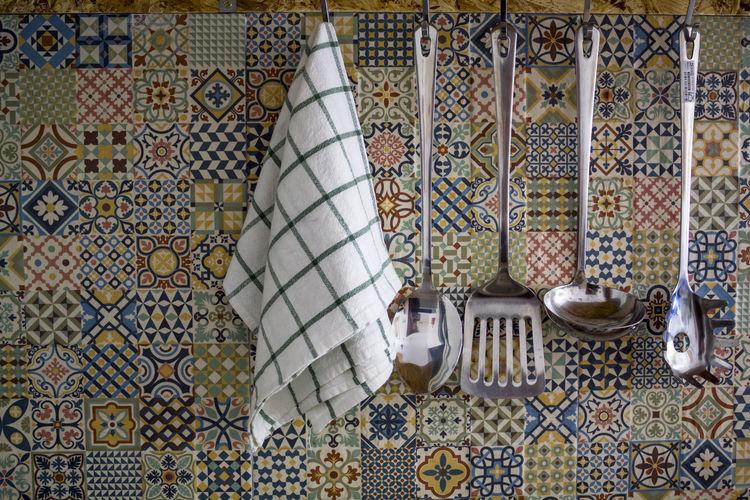 Kitchen utensils and kitchen towel hanging on kitchen wall