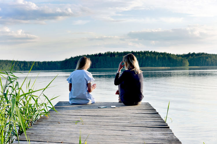 Rear view of women sitting on pier over lake against sky