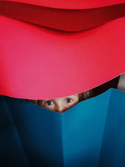 Close-up portrait of woman hiding behind curtain
