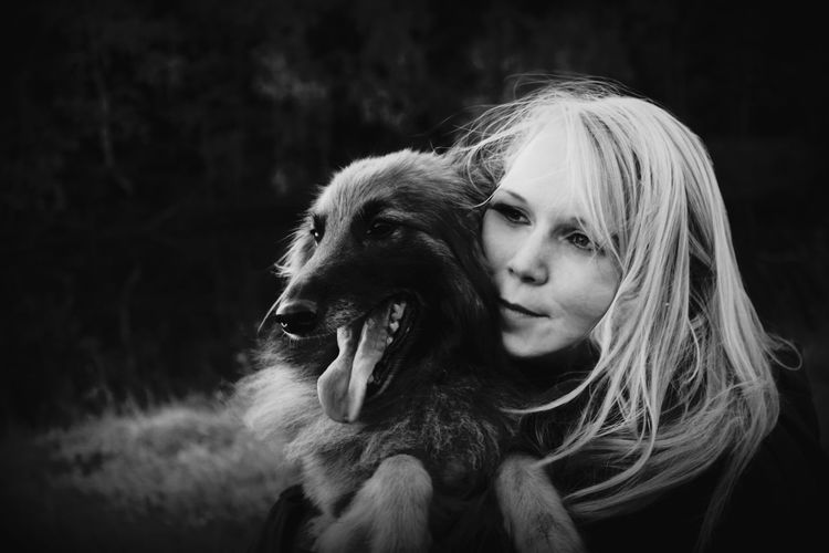 Close-up of young woman embracing dog on field