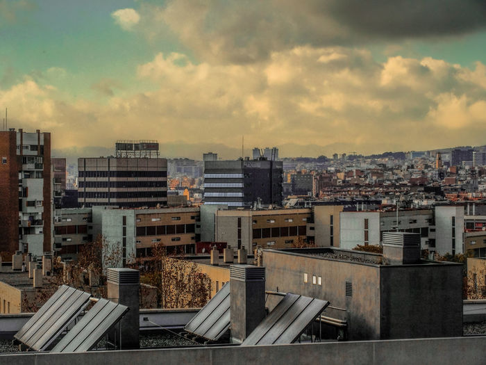 High angle view of barcelona cityscape against cloudy sky
