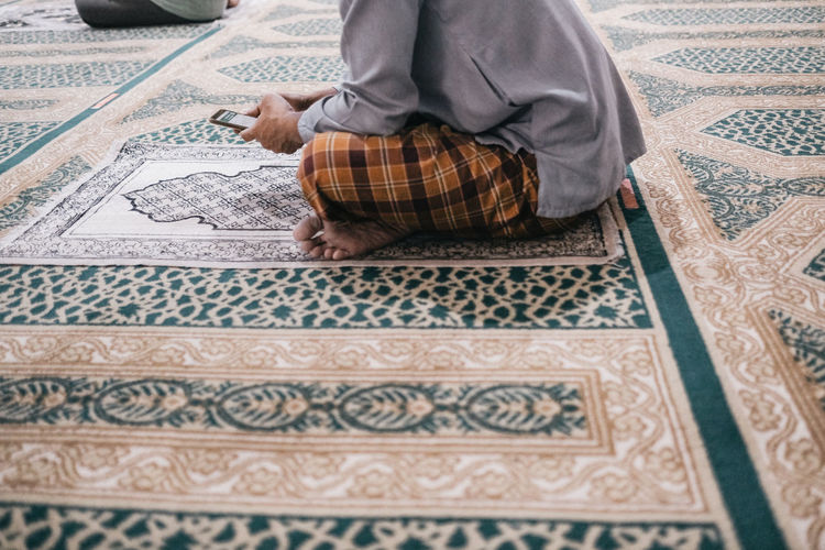 Low section of man sitting on carpet