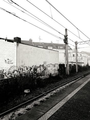 Transportation No People Outdoors Electricity  Köln Train Station Black & White Weekend Grafiti Art Foggy Day Cold Temperature Memories City Life Traveling The World Germany🇩🇪 Citytrip Holiday Photography Station Grey Grey Sky Houses Cologne , Köln,  Day
