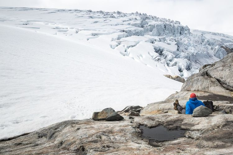 High angle view of man resting on snow covered mountain