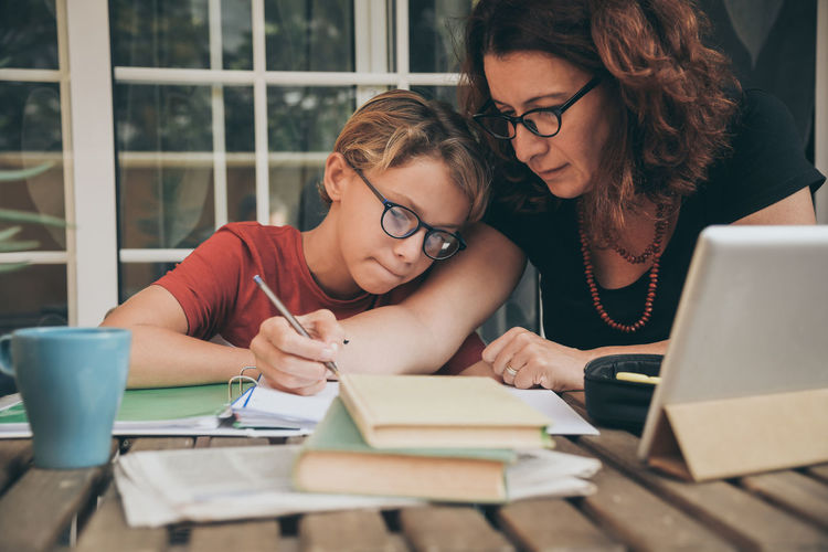 Mother teaching son while sitting by table at home