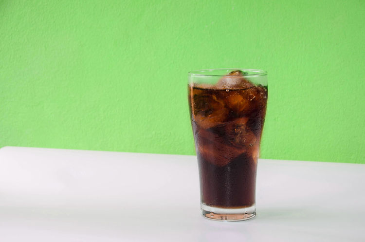 Cola cup Aerated soft drink Refreshing with ice cubes on green bright background Aerated Close-up Cola Drink Drinking Glass Food Food And Drink Freshness Green Color No People Refreshing Refreshing Drink Refreshingdrink Refreshment Soft Drink Studio Shot