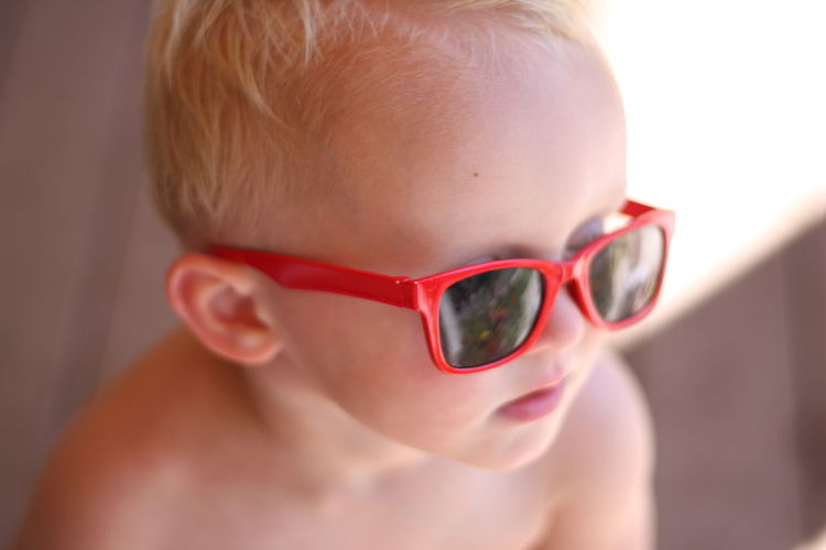 Close-up of shirtless boy wearing sunglass at home